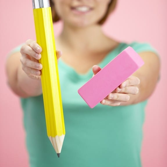 woman handing over a huge pencil and eraser
