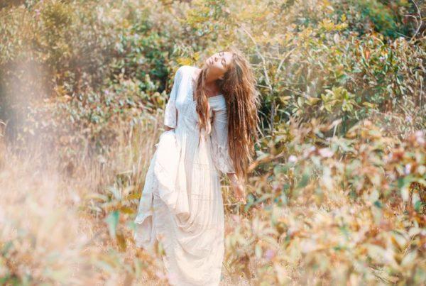 Woman in white Dress Dancing in Field