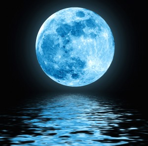 Full blue moon over water with reflections