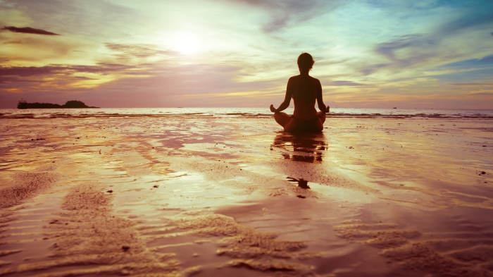 woman meditating on a sunset beach