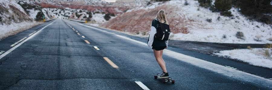 Girl skateboarding down empty road
