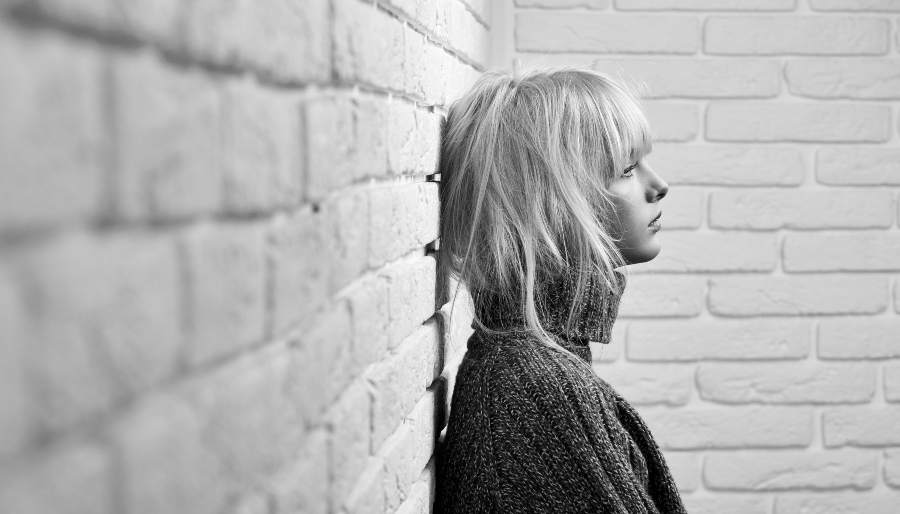 Anxious Woman leaning on a wall