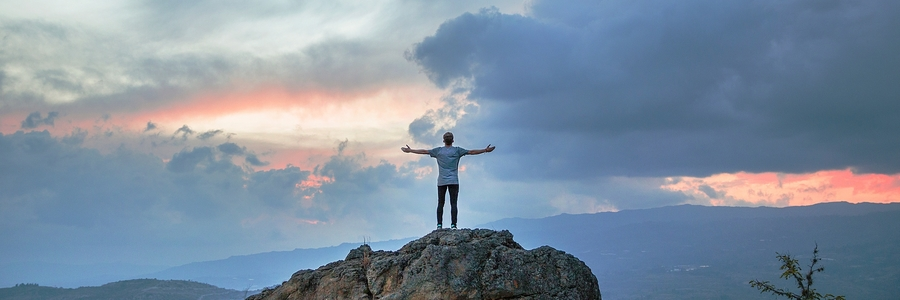 Man on Mountaintop with outstretched arms.