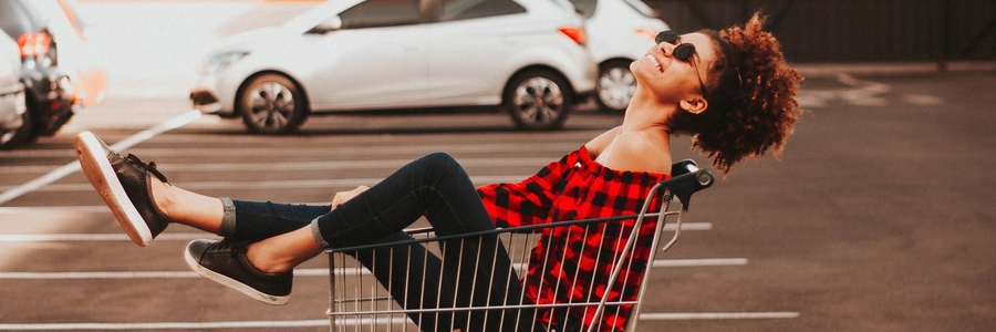 Woman Sitting In Shopping Trolly Laughing