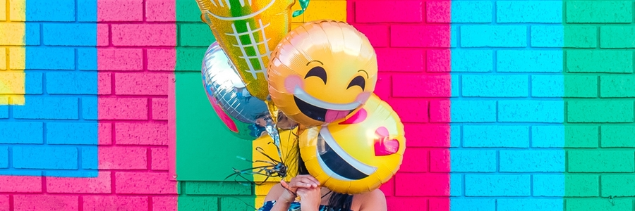 Bright Painted Wall & Smiley Balloons covering womans face