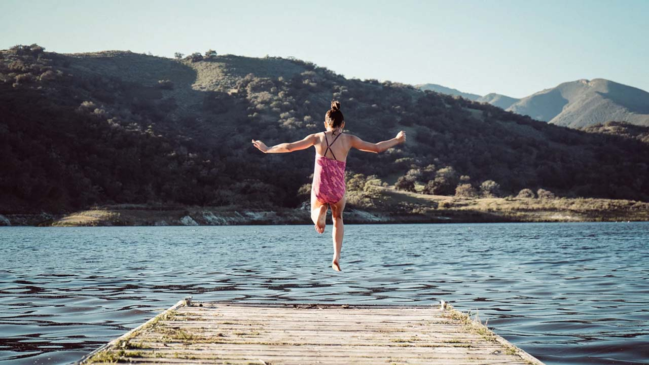 Young girl running and jumping into lake without fear of the unknown