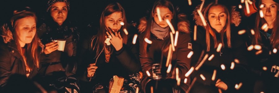 girls sitting around bonfire with marshmallows and warm jackets