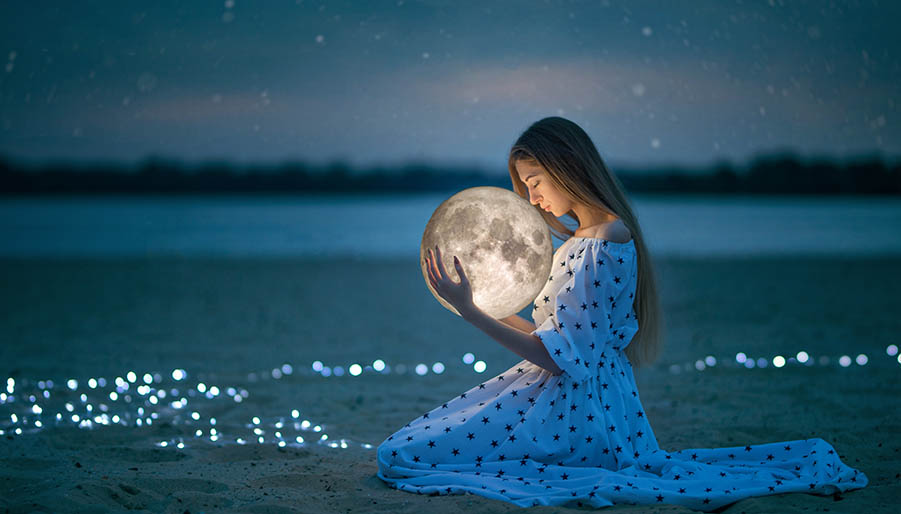 woman at night holding the moon looking at the stars