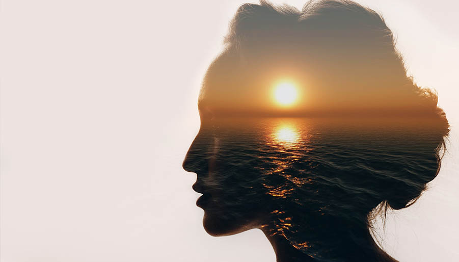 Dramatic image of a womens facial silhouette featuring a sunset over water