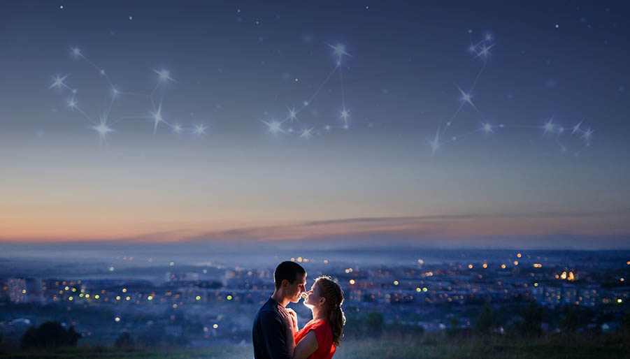 couple standing under starry sky with zodiac signs